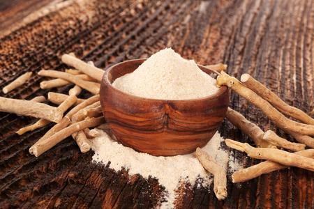 Hoop Ashwagandha-poeder in houten kom met wortels. Superfood remedie.