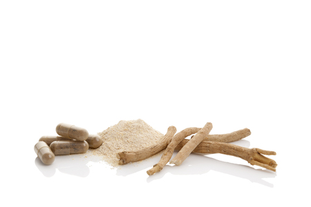 Ashwagandha roots, powder and gel capsules. Isolated on white background. Superfood remedy.
