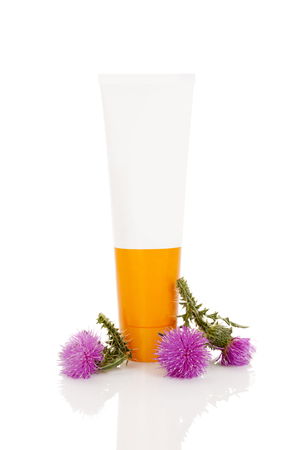 Carduus creme in tube with carduus flowers isolated on white background. Medical herb.
