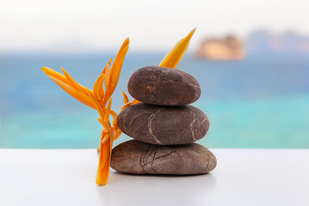 Rock cairn with tropical flour, turquise ocean in background.  Zen, balance, spa, spirituality. Stone tower, stone stack.  Stockfoto