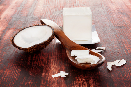 Healthy coconut oil for hair. Coconut flakes in spoon on wooden table. Hard coconut oil cube.