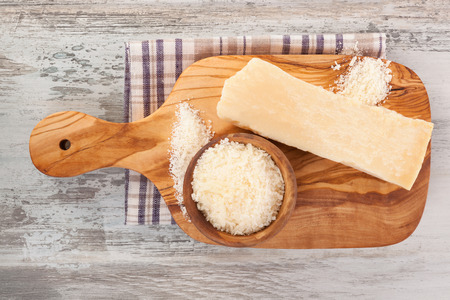 Delicious healthy shreded Parmesan cheese on wooden board from above on wooden table. Culinary cheese eating. Stock Photo