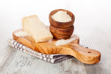 Delicious shreded Parmesan cheese with grater on wooden table. Culinary parmigiano cheese eating. Stock Photo