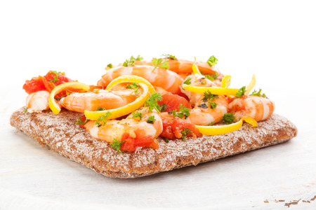 Shrimps on healthy bread with lemon and tomato sauce.