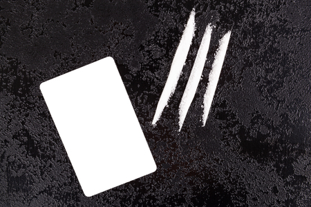 Cocaine lines with blank white card on dark surface from above. Stock Photo