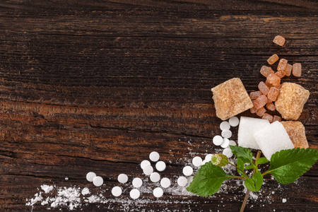 Various types of sugar with aztec sweet herb leaves from above on wooden table with copy space. Stock Photo