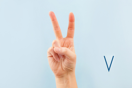 American sign language. Female hand showing letter V isolated on blue background.