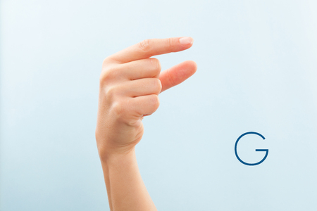 American sign language. Female hand showing letter G isolated on blue background.  스톡 콘텐츠