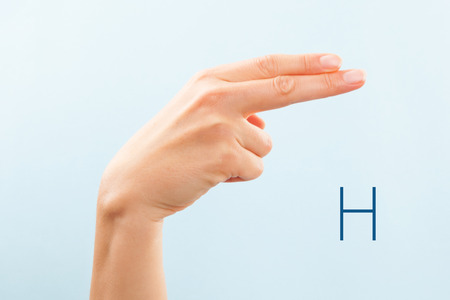 American sign language. Female hand showing letter H isolated on blue background.  Stock Photo