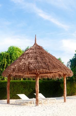 Beach hut wiht deck chairs on white sandy beach. Luxurious vacation.