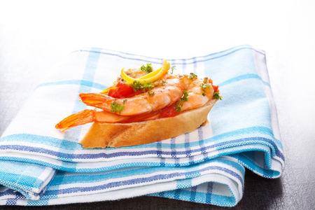 Appetizer canape with shrimps on cloth. Mediterranean seafood eating. Stock Photo