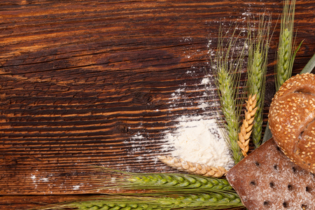 Wholegrain pastry with barley and wheat spikes on wooden table from above.