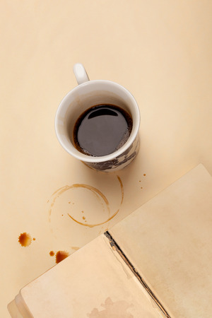 Writers block. Half empty cup of coffee and old book with empty page on beige table with coffee stains.