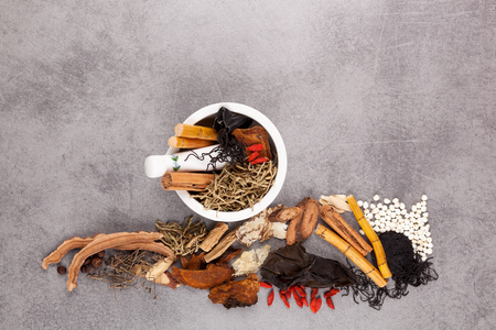Different kind of Chinese herbal and mortar on gray background.