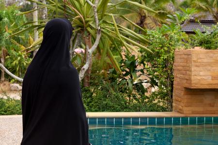 Arabic woman with black hijab or burka headscarf at pool in luxurious tropical resort. Stok Fotoğraf