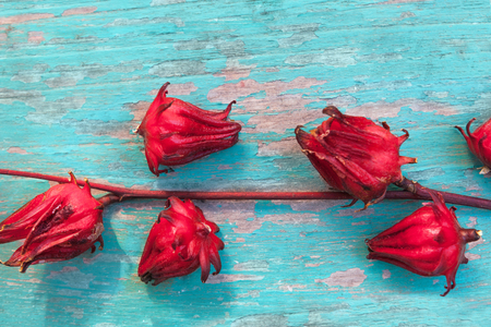 Fresh Roselle fruits from above on wooden table.