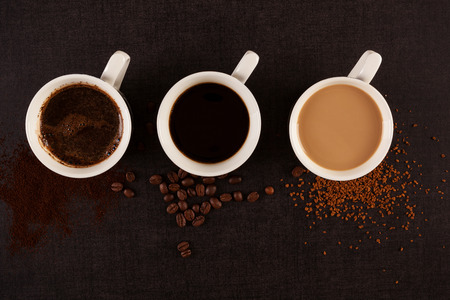 Three cups of coffe with ground, instant coffee and roasted beans on dark background from above.