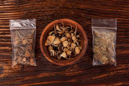 Dry psilocybin magic mushrooms and marijuana buds in plastic bags on brown table. Medical alternative remedy. Stock Photo