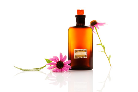 Echinacea flowers with extract in medicinal brown glass jar isolated on white background.