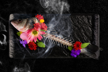 Skelet of fish with flowers and smoke. Conscious Eating.