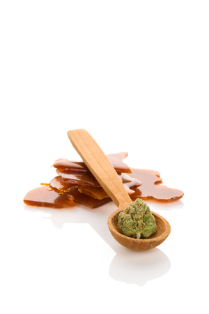 Cannabis bud on wooden spoon and shatter concentrate isolated on white background. Banco de Imagens
