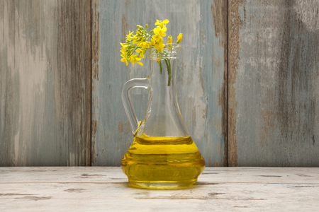 Rapeseed oil in jar and oilseed rape flowers on wooden background. Canola oil.
