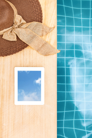 Sunhat and Tablet near blue swimming pool in summer from above.