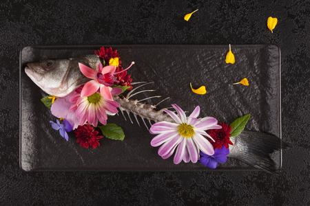 Fischskelett mit Blumen von oben. Kunst auf dem Teller. Standard-Bild