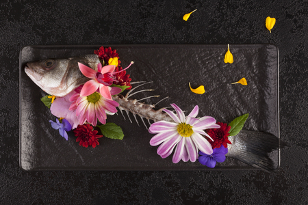 Skelet of fish with flowers from above. Art on the plate. Standard-Bild - 117780042