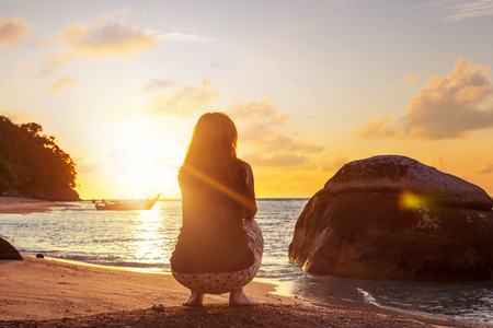 Woman sitting in deep squat on sandy beach against beautiful sunset. Relaxing. Stock Photo