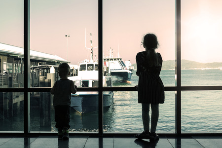 Young brother and sister waiting for boat without parents in dock. Adventure, trip. Travelling with kids.