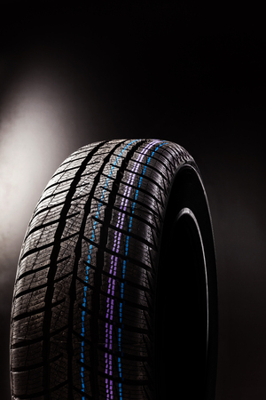 Brand new winter tyre isolated on grey background.