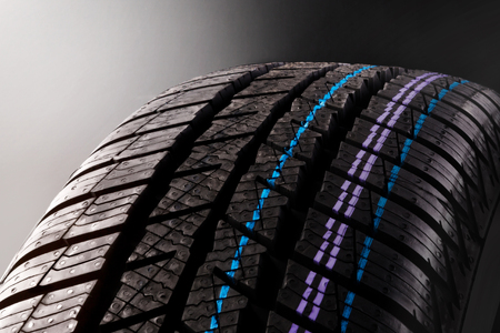 New snow tire tread design detail isolated on dark background.