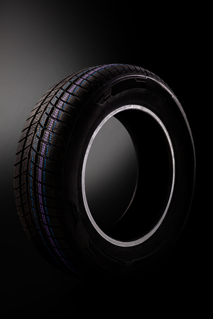 New car tire isolated on dark background.