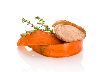 Roast duck with red kuri squash and herbs isolated on white background. Culinary gourmet festive eating.