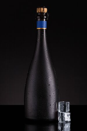 Dewy champagne bottle with ice on black background. Luxury celebration.