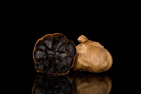 Black garlic on dark background. Culinary food ingredient. Reklamní fotografie