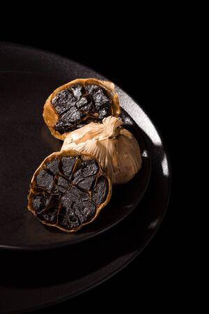 Black garlic on black plate on dark background. Culinary food ingredient.