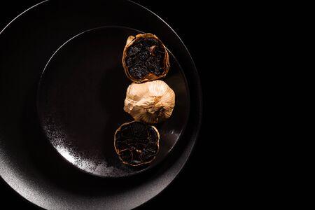 Black garlic on black plate on dark background from above. Culinary food ingredient. Reklamní fotografie