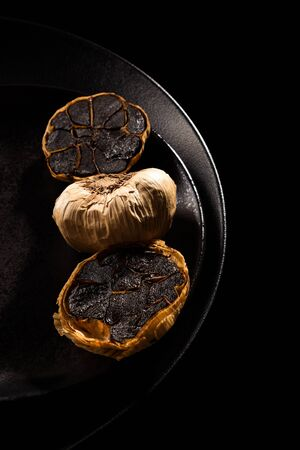 Whole and sliced black garlic on black plate on dark background from above. Culinary food ingredient. Reklamní fotografie
