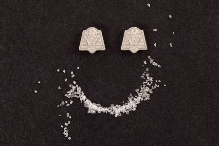 MDMA crystal and ecstasy pills forming smiley face.