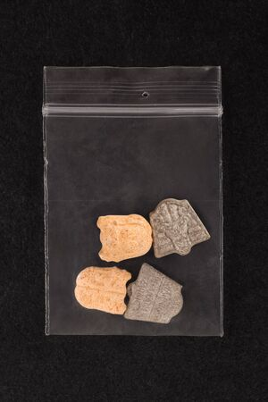 Ecstasy pills in plastic bag on black background from above.