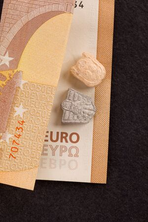 Ecstasy pills on euro bill, top view. Dealing drugs.