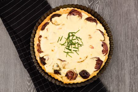 Homemade sheep cheese Quiche with red onion ready to eat flaty lay on table, top shot. Healthy food eating. Banco de Imagens