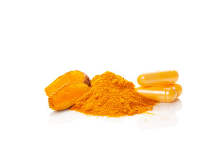 Turmeric (curcumin) powder heap, capsules and fresh turmeric rhizome isolated on a white background.