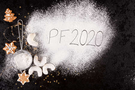 Holiday background. Christmas concept with gingerbreads, christmas cookies, sifter, spilled sugar and the letters PF 2020 from above.