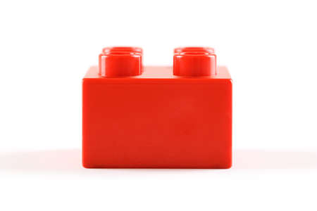 Red plastic lego/duplo block on white background. Concept of simplicity and children's creativity.