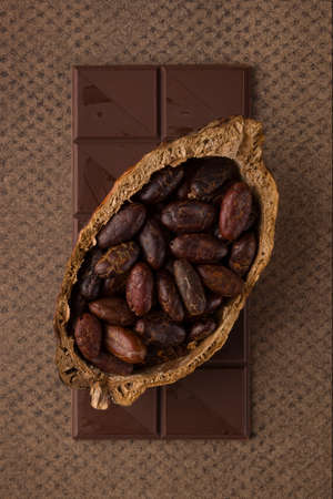 Chocolate bar and cocoa beans on brown background. Luxurious dark mood background.