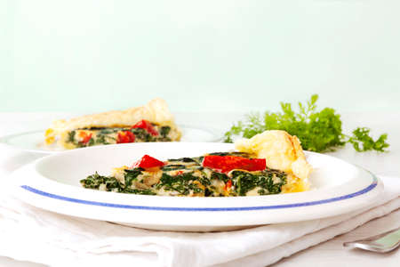 Piece of pie with spinach and tomatoes. Culinary vegetarian food. Satly cake.