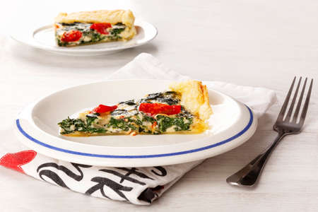 Vegetarian quiche. Piece of pie with spinach and tomatoes. Culinary eating. Stok Fotoğraf